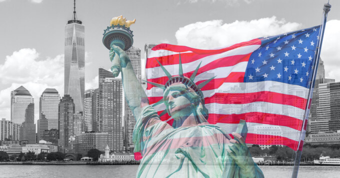 Statue of Liberty with a large american flag and New York skyline in the background
